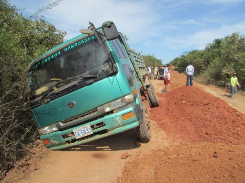 Lorry carrying soil goes off the mud road trying to avoid the soil piles (centre)