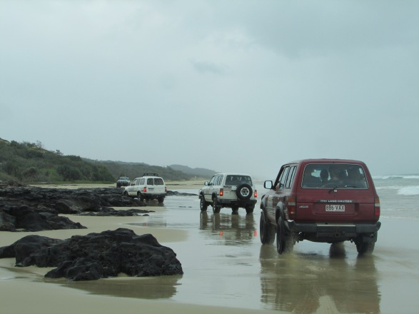 A traffic jam - the cars ahead waiting for the waves t go out before heading around the rocks